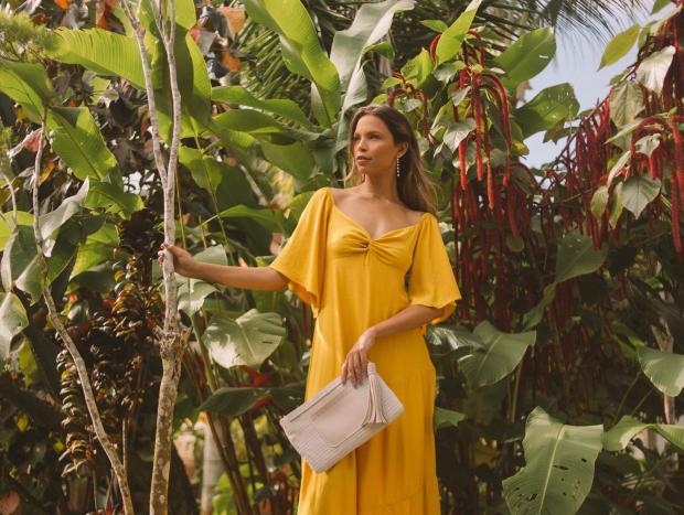 девушка в длинном желтом платье с белой сумкой