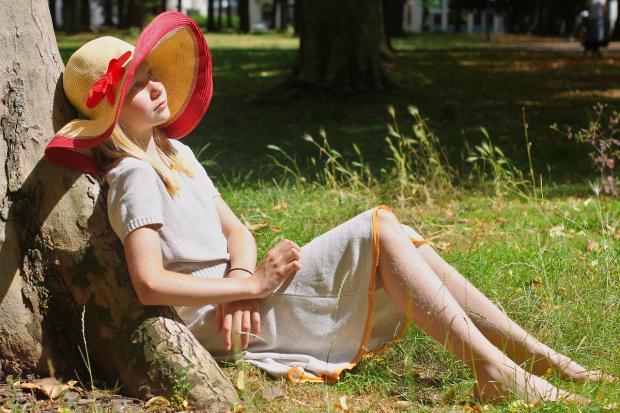 девушка в платье и шляпе сидит на траве под деревом