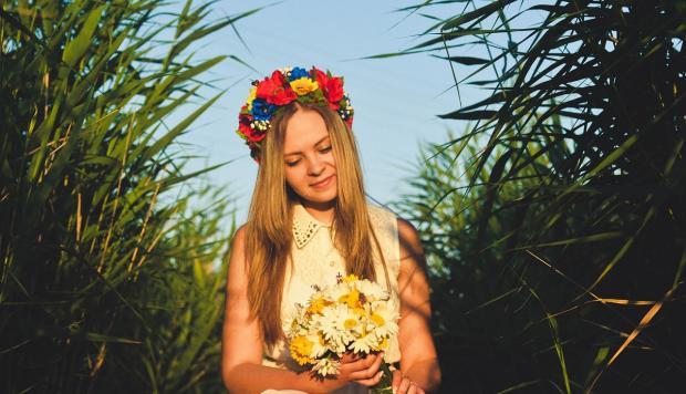 девушка в венке на голове держит в руках цветы