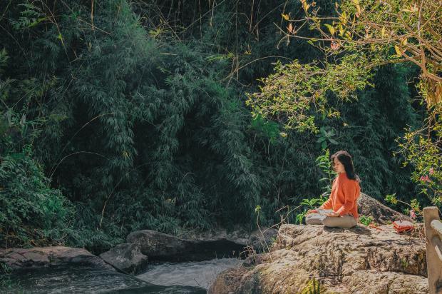 девушка сидит на камне на берегу реки