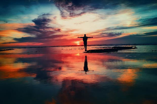 человек стоит на берегу океана на закате