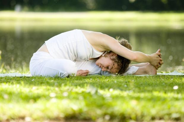 девушка в белом костюме делает растяжку на траве