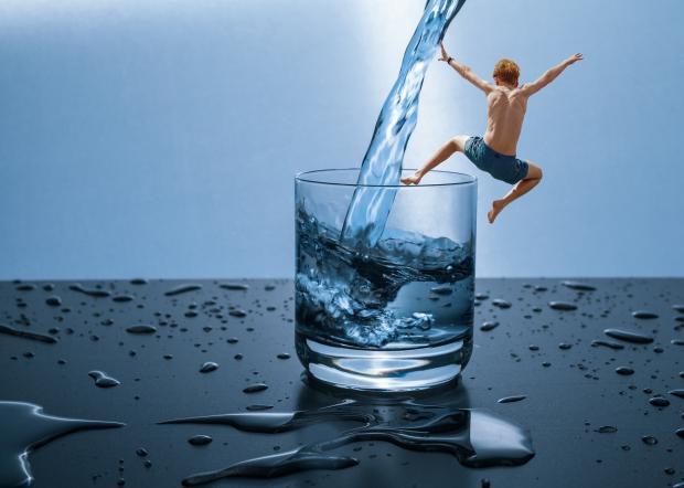 стакан с водой, прыгающий в него человек