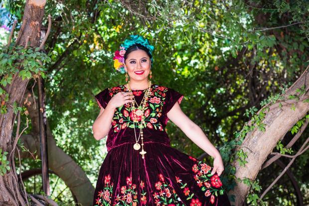 нарядно одетая девушка стоит в тени дерева