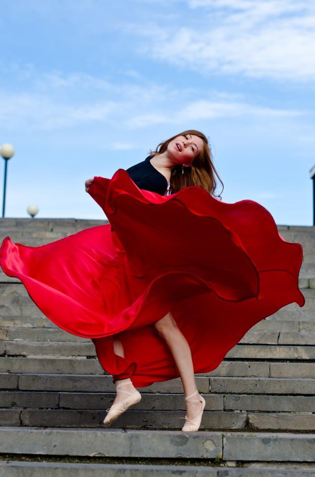 танцует девушка в длинной и широкой  красной юбке