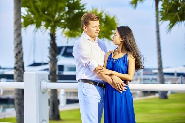 мужчина в белой рубашке обнимает девушку в синем сарафане