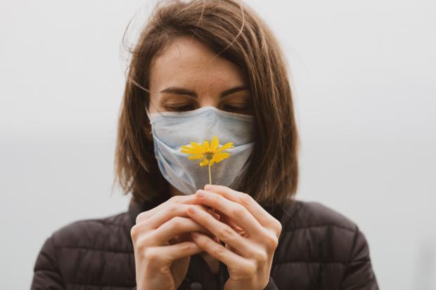 девушка в маске нюхает цветок