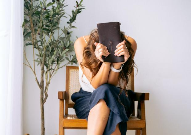 Девушка в белой майке и синих джинсах сидит и закрывает лицо книгой