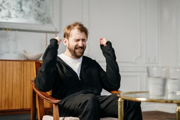 мужчина в темном свитере сидит в кресле