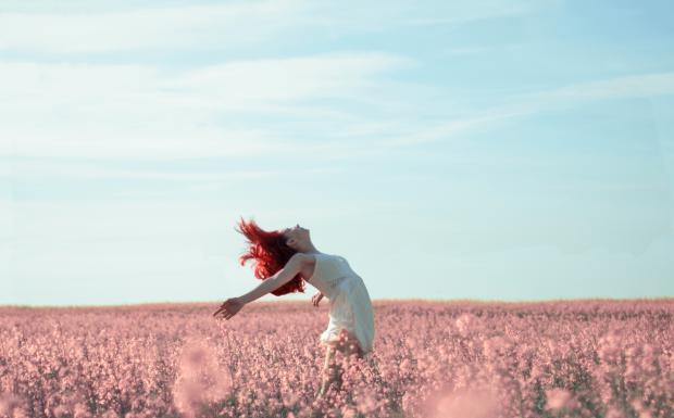 девушка с красными волосами на цветущем поле
