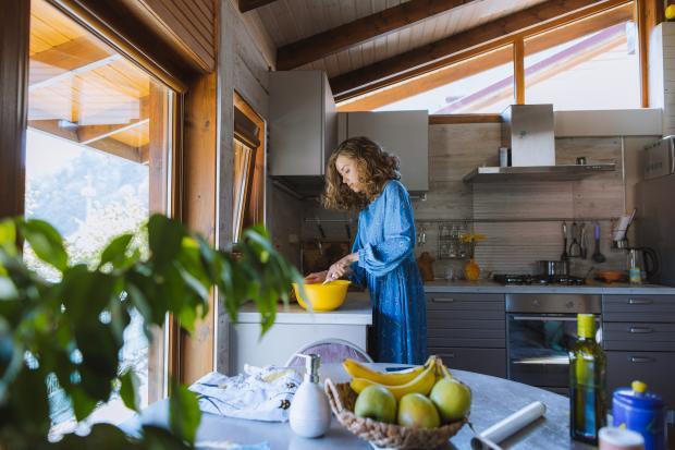 девушка в синем платье готовит на кухне