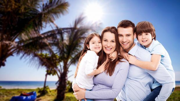 родите и двое детей на фоне пальмы