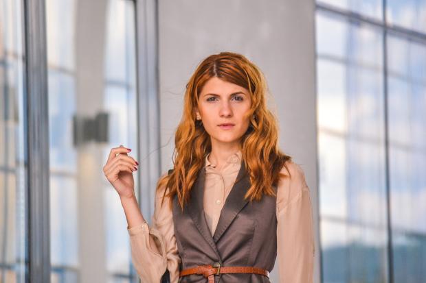 рыжеволосая девушка в офисном костюме работает