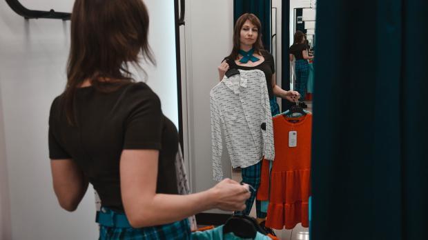девушка примеряет наряды в магазине