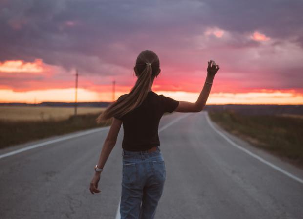 девушка в футболке и джинсах на фоне заката идет по дороге