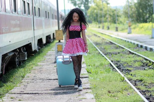 брюнетка с кудрявыми волосами в нарядном платье идет по перрону с чемоданом