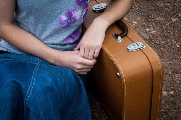девушки сидит опираясь на чемодан