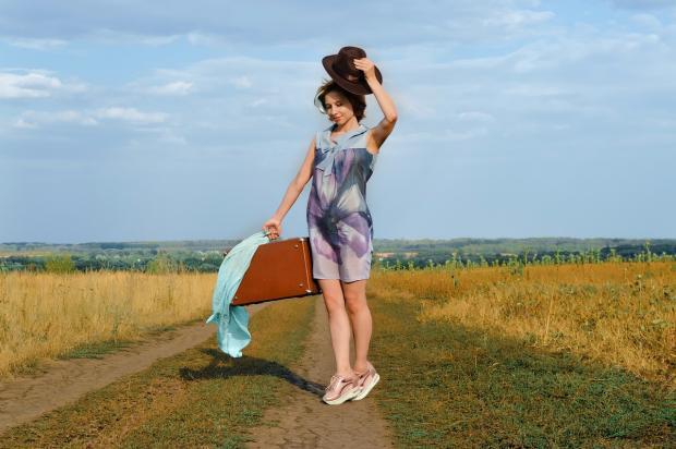 девушка стоит на дороге в поле с чемоданом