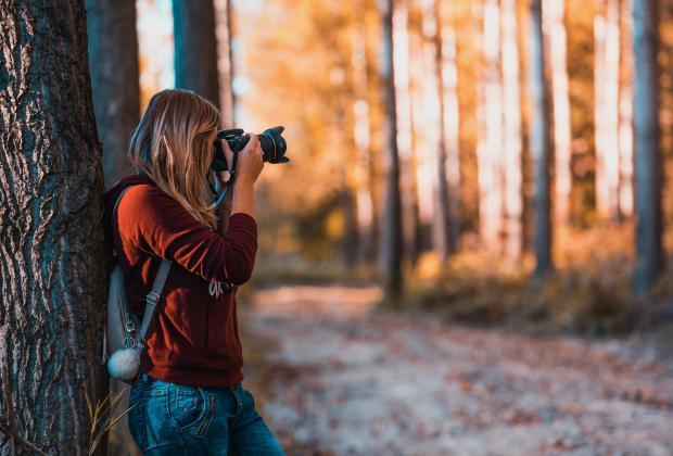 девушка с фотоаппаратом в лесу
