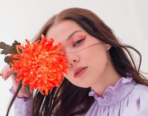 девушка в розовом платье и с ярким макияжем прикрывает лицо красным цветком