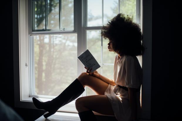 девушка читает книгу сидя на подоконнике