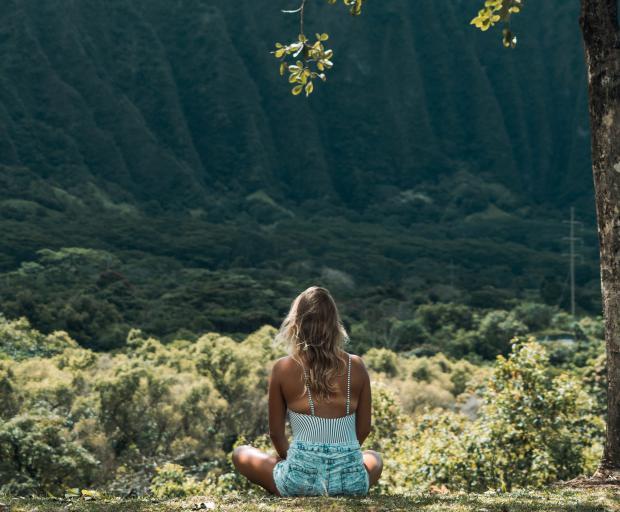 молодая девушка со светлыми волосами сидит на природе