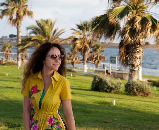 девушка в желтом платье и солнцезащитных очках стоит рядом с пальмами