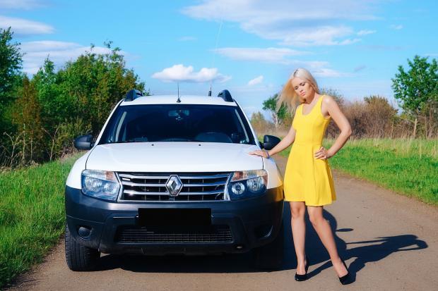 блондинка в желтом платье стоит рядом с автомобилем