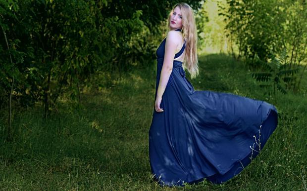 блондинка стоит на зеленой траве в развевающемся на ветру синем сарафане
