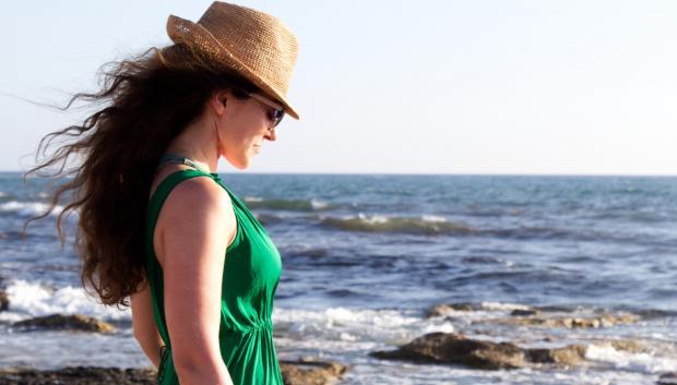 девушка в зеленом платье и соломенной шляпе стоит у моря