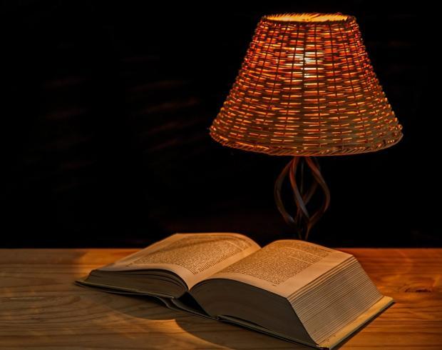 под красивой настольной лампой с абажуром лежит раскрытая книга