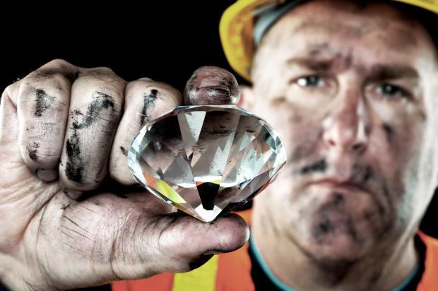 мужчина держит драгоценный камень