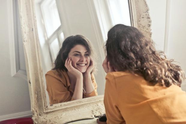 длинноволосая девушка смотрит в зеркало и смеется