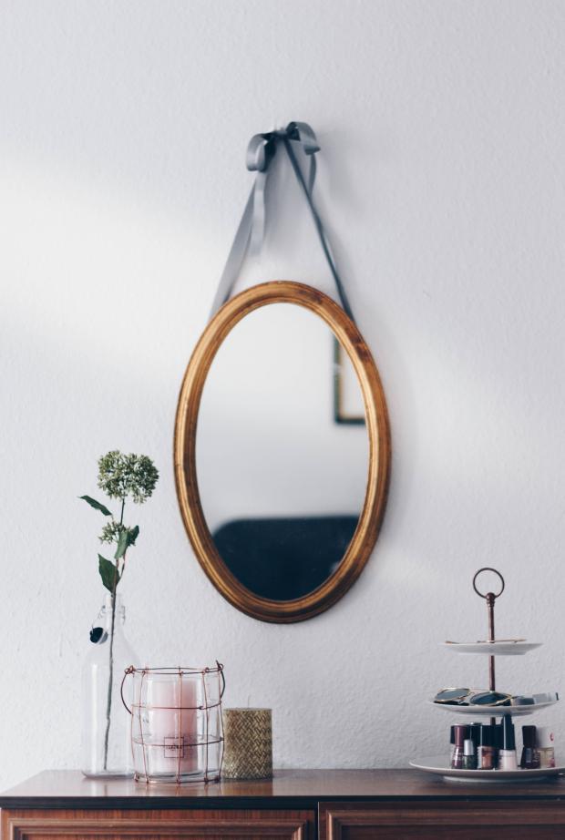 овальное зеркало в рамке висит на белой стене