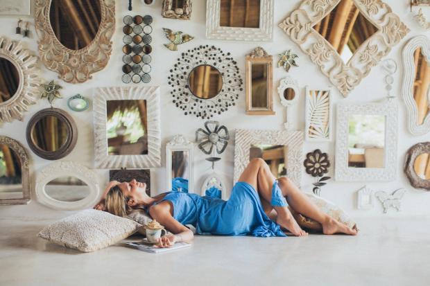 женщина в голубом сарафане лежит около увешанной зеркалами стены