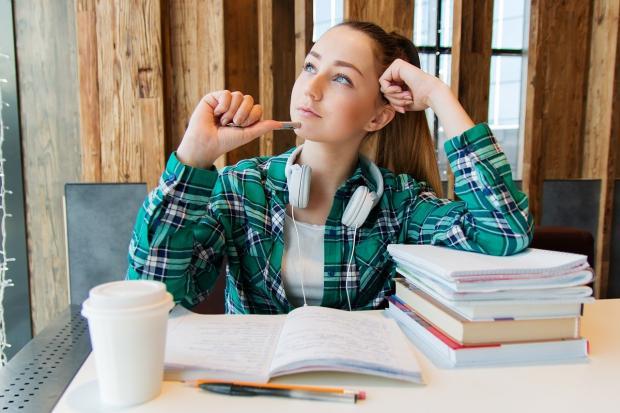 студентка в зеленой клетчатой рубашке готовится к семинару