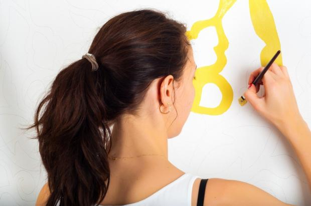 девушка с прической конский хвост рисует желтыми красками на стене