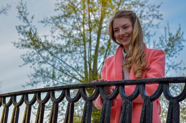 смеется девушка в розовом у кованой ограды на мосту