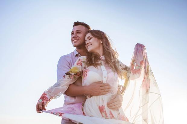 мужчина и девушка в летнем платье обнимаются и смеются