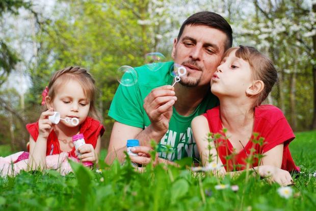 папа с дочками в красных футболках играет с одуванчиками на траве