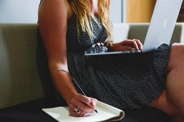 девушка в сарафане сидит на диване и пишет в тетрадь