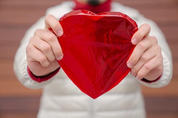 сердце из фольги в руках мужчины