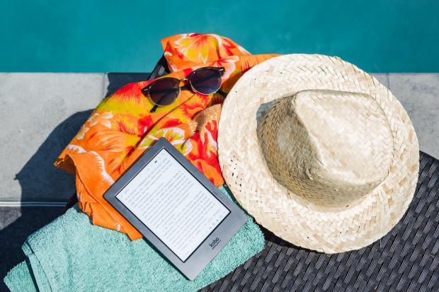 шляпа, солнцезащитные очки, парео и книга у бассейна