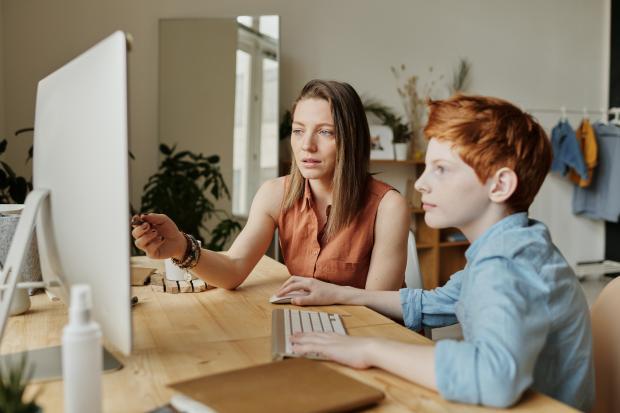 женщина и мальчик сидят перед компьютером