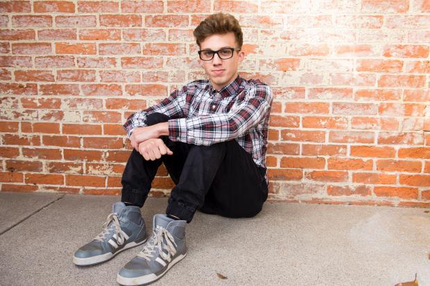 молодой мужчина в клетчатой рубашке сидит возле кирпичной стены