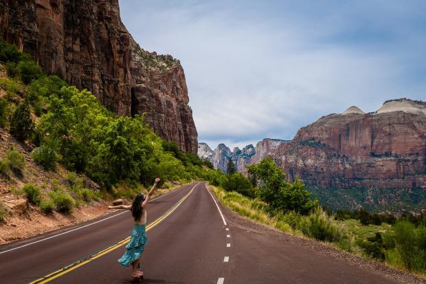 девушка идет по шоссе в горах с поднятыми к небу руками