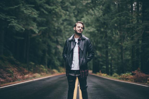 мужчина стоит на дороге в лесу