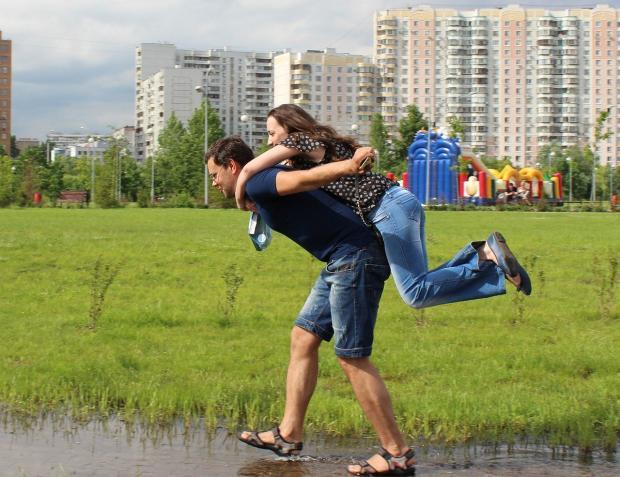 мужчина переносит девушку через лужу