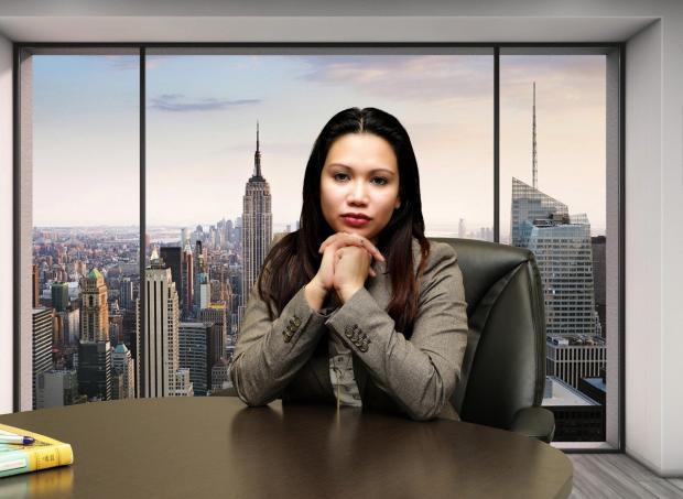 за письменным столом сидит бизнес-вумен