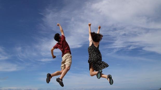 мужчина и девушка подпрыгнули на фоне голубого неба